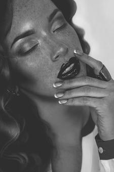 Pionowe czarno-białe zdjęcie dziewczyny z piegami