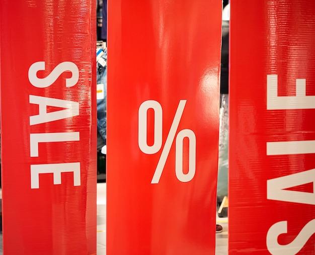 Pionowe czerwone banery przy wejściu do sklepu z napisami sprzedaż i znakiem procentu