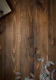 Pionowe drewniane tło z notatnikiem i kolorowymi spinaczami