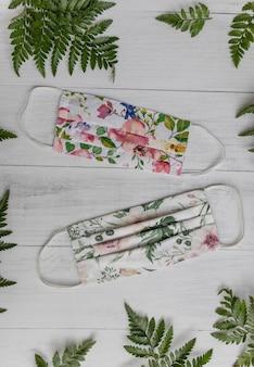 Pionowe, duże ujęcie masek na twarz z motywem kwiatowym i zielonymi liśćmi na drewnianej powierzchni