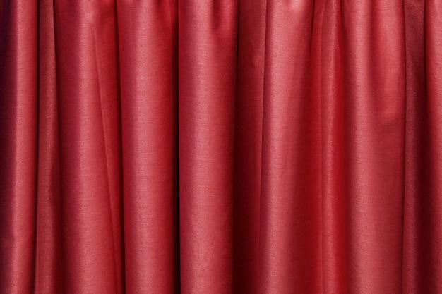 Pionowe fałdy z bordowej tkaniny. streszczenie tekstura tkaniny.