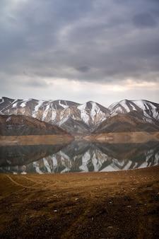 Pionowe, malownicze ujęcie pasma górskiego odbitego w wodach zbiornika azat w armenii