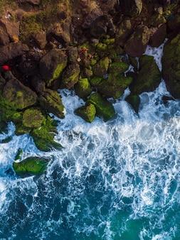 Pionowe napowietrzne ujęcie lotnicze falistego błękitnego morza na tle skał