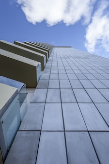Pionowe niski kąt ujęcia wysokiego budynku ze szklanymi balkonami pod pięknym niebieskim niebem