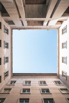 Pionowe, niskie ujęcie kwadratu z niebem uformowanym przez budynki
