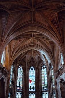 Pionowe, niskie ujęcie pięknego sufitu i okien starej katedry