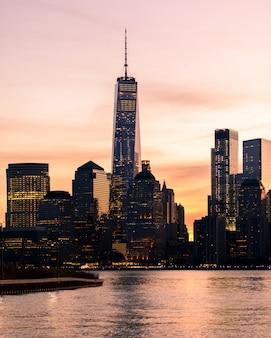 Pionowe odległe ujęcie budynku world trade center w nowym jorku podczas zachodu słońca