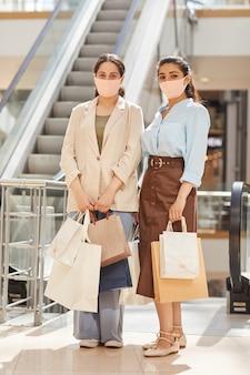 Pionowe pełnej długości portret dwóch młodych kobiet noszących maski podczas zakupów w centrum handlowym i