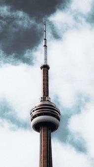 Pionowe piękne ujęcie szczytu wieży radiowej pod ponurym, pochmurnym, szarym niebem