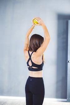 Pionowe płytkie fokus strzał kobiety w sportowej ćwiczeń z piłką