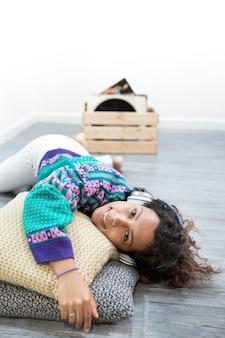 Pionowe portret hispanic kobiety słuchania muzyki w domu. miejsce na tekst.
