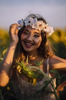 Pionowe portret kobiety brunetka w szelki kwiatowe wrona pochylony do przodu uśmiechnięty w słonecznikowym polu