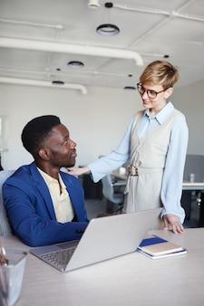 Pionowe portret uśmiechnięta kobieta menedżer rozmawia z afroamerykańskim kolegą stojącym przy nim i uśmiechnięta, kopia przestrzeń