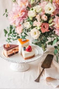 Pionowe selektywne skupienie stojaka na ciasto z smacznymi kawałkami ciasta