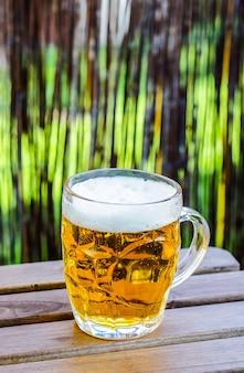 Pionowe selektywne zbliżenie kubka piwa na drewnianym stole