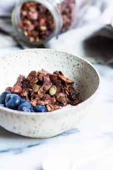 Pionowe strzał granola paleo kakaowa i jagody w białej misce z rozmytym tłem