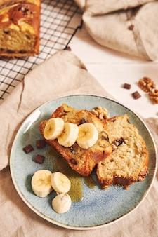 Pionowe strzał kromki pysznego chleba bananowego z kawałkami czekolady i orzechami na talerzu