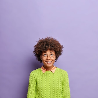 Pionowe strzał szczęśliwa młoda kobieta z kręconymi włosami uśmiecha się szeroko skoncentrowane powyżej
