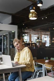 Pionowe strzał uśmiechnięta atrakcyjna dziewczyna siedzi w kawiarni z laptopem, patrząc na kamery.