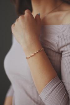 Pionowe strzał zbliżenie kobiety ubrana w złotą bransoletkę