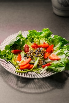 Pionowe strzał zbliżenie naczynia wegetariańskie z truskawkami reklam sałaty