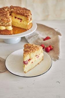 Pionowe strzał zbliżenie pyszne ciasto waniliowe z truskawkami wewnątrz na białym stole