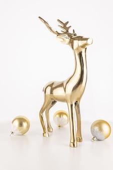Pionowe strzał złotego posągu jelenia z kulkami ozdoba christmas samodzielnie na białym tle