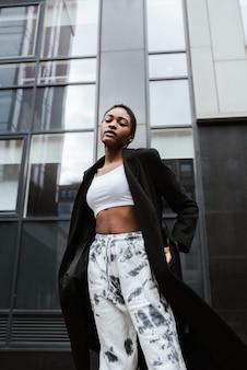 Pionowe ujęcie african-american kobieta ubrana w płaszcz i pozowanie na ulicy