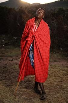 Pionowe ujęcie afrykańskiego mężczyzny z kocem wokół niego, trzymającego kij