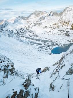 Pionowe ujęcie alpinisty wspinającego się na pokryte śniegiem tatry w polsce