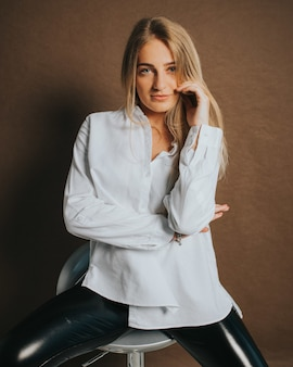 Pionowe ujęcie atrakcyjnej blondynki kobiety pozującej siedząc na stołku barowym