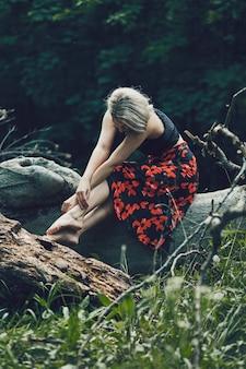 Pionowe ujęcie atrakcyjnej blondynki kobiety z kwiecistą suknią siedzącą na kłodzie drzewa, patrzącą w dół