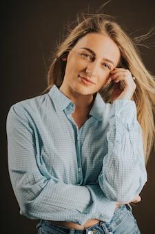 Pionowe ujęcie atrakcyjnej blondynki w dżinsach i krótkiej koszuli pozującej na brązowym tle