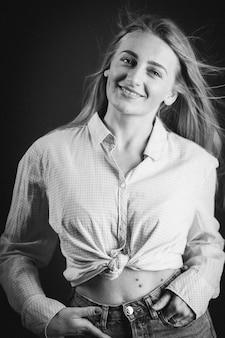 Pionowe ujęcie atrakcyjnej blondynki w dżinsach i krótkiej koszuli pozującej na czarnej ścianie