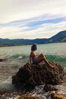 Pionowe ujęcie atrakcyjnej kobiety siedzącej na formacji skalnej z pięknym dniem