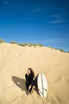 Pionowe ujęcie atrakcyjnej kobiety siedzącej na piaszczystym wzgórzu z deską surfingową na boku