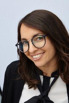 Pionowe ujęcie atrakcyjnej kobiety uśmiechając się do kamery