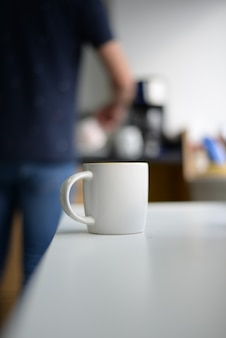 Pionowe ujęcie białego kubka do kawy na stole
