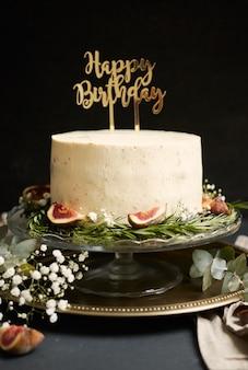 Pionowe ujęcie białego tortu wszystkiego najlepszego z okazji urodzin z zielonymi liśćmi na dole