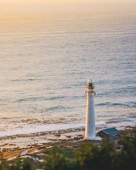 Pionowe ujęcie białej latarni morskiej na pięknym brzegu w pobliżu akwenu.