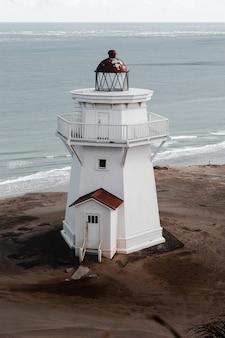 Pionowe ujęcie białej latarni morskiej na wybrzeżu