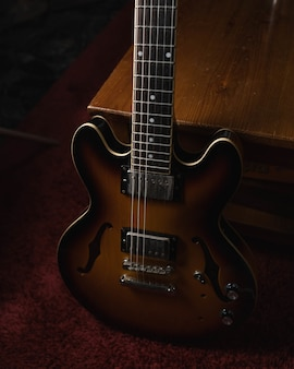 Pionowe ujęcie brązowej gitary akustycznej na ziemi