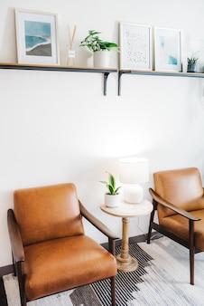 Pionowe ujęcie brązowych krzeseł z białą lampą i rośliną domową w stole
