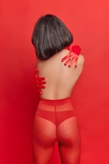 Pionowe ujęcie brunetki bez twarzy, która obejmuje się, stoi z pół nagim ciałem, ma idealną figurę seksualną, nosi majtki i czerwone rajstopy