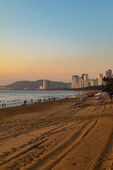 Pionowe ujęcie brzegu plaży z ludźmi chodzącymi w nha trang