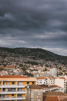 Pionowe ujęcie budynków na górze pod zachmurzonym niebem w funchal, madera, portugalia.