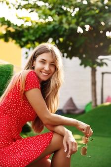 Pionowe ujęcie całkiem blond dziewczyny siedzącej w zielonym parku w letni dzień, ubrana w sukienkę i trzymając okulary przeciwsłoneczne, odwróć się do aparatu, aby się uśmiechnąć