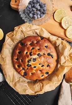 Pionowe ujęcie cherry cake z cukrem pudrem i składnikami