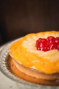 Pionowe ujęcie ciasta biszkoptowego z wiśniami na wierzchu na marmurowym stole