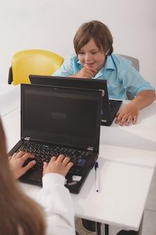 Pionowe ujęcie cute zabawnego chłopca studiującego na swoim komputerze w klasie